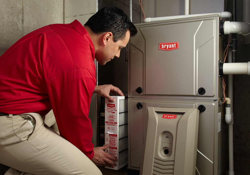 Bryant Heating and Cooling Tech performing furnace maintenance