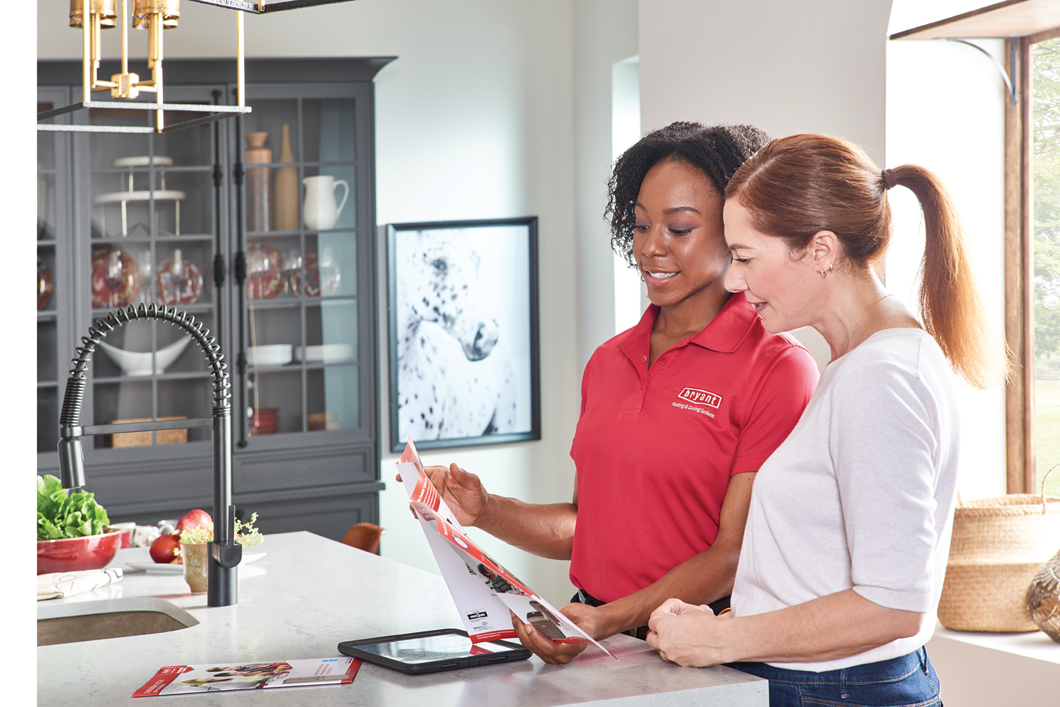 Bryant Heating and Cooling Tech with homeowner in kitchen